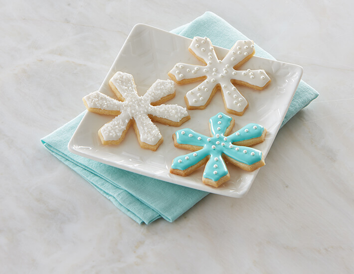 Pretty Snowflake Sugar Cookies from Cake Mate made with Cookie Icing Shimmering White Decorating Sugars and Pearls for the holidays